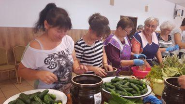 Zdjęcie przedstawia grupę osób przy zastawionym stole, przygotowujących ogórki do kiszenia.