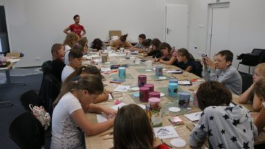 Zdjęcie przedstawia grupę dzieci siedzącą przy dużym stole podczas warsztatów decoupage.