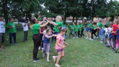 Zdjęcie przedstawia grupę dzieci i dorosłych podczas zabaw ruchowych w parku.