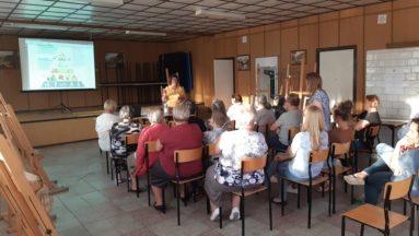 Zdjęcie przedstawia salę z publicznością oglądającą prezentację.