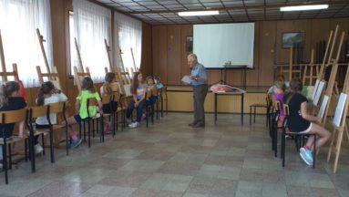 Zdjęcie przedstawia widok wnętrza. Po obu stronach sali dzieci siedzą w rzędzie przy sztalugach, malując; pomiędzy dwoma rzędami sztalug stoi instruktor zajęć.