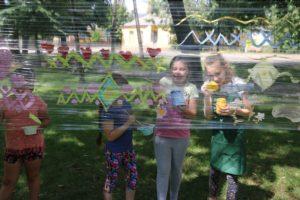 Zdjęcie przedstawia dzieci wparku, malujące naprzeźroczystej folii rozłożonej między drzewami.