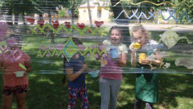 Zdjęcie przedstawia dzieci w parku, malujące na przeźroczystej folii rozłożonej między drzewami.