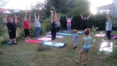 Zdjęcie przedstawia grupę osób w plenerze, stojących na matach do jogi i wspólnie wykonujących ćwiczenie.