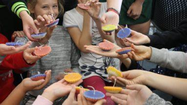 Zdjęcie przedstawia grupę dzieci prezentujących własnoręcznie wykonane świece.