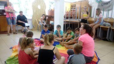 Na zdjęciu widzimy grupę dzieci wraz z dwoma instruktorkami zajęć, siedzącymi w kole na kolorowym kocu w pomieszczeniu.