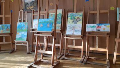 zdjęcie przedstawia obrazy na sztalugach, stojących pod ścianą w pomieszczeniu.