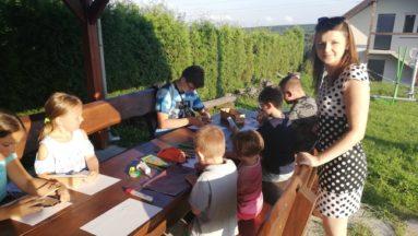 Zdjęcie przedstawia dzieci rysujące przy stole w plenerze. Obok stołu stoi koordynatorka zajęć.