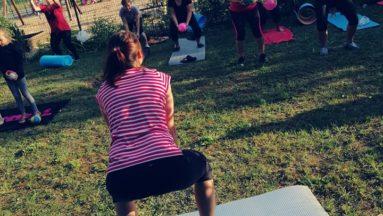 Zdjęcie przedstawia grupę osób w plenerze, wykonujących ćwiczenia na matach do jogi. Na pierwszym planie widzimy instruktorkę zajęć, a w tle - grupę uczestników.