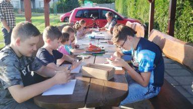 Zdjęcie przedstawia dzieci rysujące przy stole w plenerze.