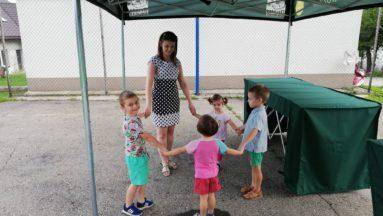 Zdjęcie przedstawia czwórkę dzieci oraz koordynatorkę zajęć, stojące w kole i trzymające się za ręce.