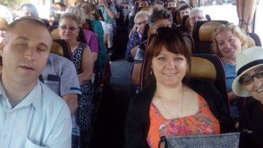 Zdjęcie przedstawia wnętrze autokaru, w którym siedzą uśmiechnięci uczestnicy wycieczki.