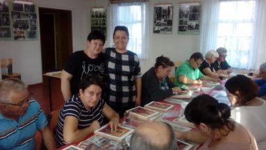Zdjęcie przedstawia uczestników warsztatów ikonograficznych, siedzących we wnętrzu przy dużym stole.