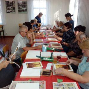 Zdjęcie przedstawia uczestników warsztatów podczas pracy nadikonami.