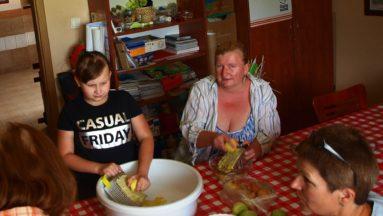 Zdjęcie przedstawia cztery kobiety siedzące przy stole. Jedna z nich uciera ziemniaki na tarce.