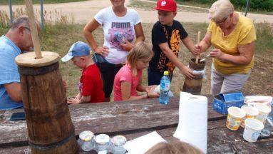 Zdjęcie przedstawia grupę dorosłych i dzieci stojących przy stole, na którym rozłożone są narzędzia do wyrobu masła.