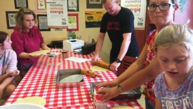 Zdjęcie przedstawia dorosłych i dzieci, siedzących przy stole i wyrabiających oraz wałkujących ciasto.