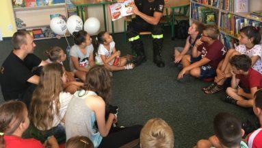Zdjęcie przedstawia grupę dzieci siedzących w kółku na podłodze w bibliotece. Obok na krześle siedzi mężczyzna w strażackim stroju, pokazujący dzieciom książkę i opowiadający o niej.