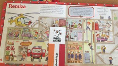 """Zdjęcie przedstawia książkę dla dzieci o strażakach otwartą na stronie zatytułowanej """"Remiza"""". Na książce leży zakładka z logiem programu """"Działaj Lokalnie""""."""