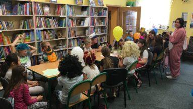 Zdjęcie przedstawia dzieci poprzebierane w różne stroje, siedzące przy stolikach w bibliotece.