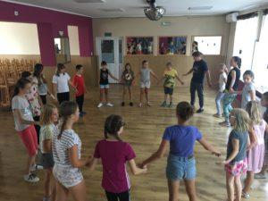 Zdjęcie przedstawia dzieci stojące wkole nastali gimnastycznej.