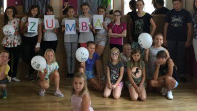 Zdjęcie przedstawia dzieci pozujące do zdjęcia na sali gimnastycznej. Piątka dzieci stojących w drugim rzędzie tryma kartki układające się w napis ZUMBA.