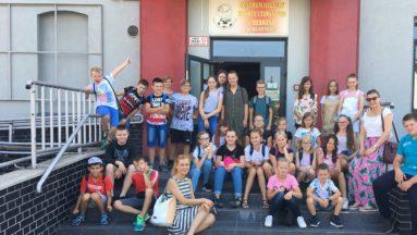 Zdjęcie przedstawia grupę dzieci, pozujących w grupie do zdjęcia przed wejściem do budynku biblioteki.