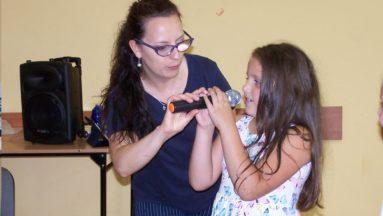 Zdjęcie przedstawia dziewczynkę trzymającą mikrofon. Obok niej stoi instruktorka zajęć.