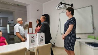 """Na zdjęciu widzimy cztery osoby stojące przy stole, na którym znajdują się torby z logiem programu """"Działaj Lokalnie""""."""