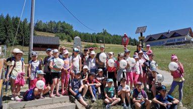 Zdjęcie przedstawia grupę dzieci w plenerze, pozujących do zdjęcia.