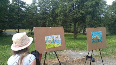 Zdjęcie przedstawia dwie sztalugi w plenerze, na których ustawione są prace malarskie wykonane przez dzieci. Na pierwszym planie znajduje się dziewczynka w kapeluszu, oglądająca prace.