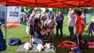 Zdjęcie przedstawia zajęcia z pierwszej pomocy, prowadzone w plenerze.