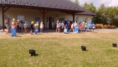 Zdjęcie przedstawia dzieci biorące udział w zabawach w ogrodzie.