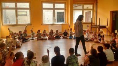 Zdjęcie przedstawia grupę dzieci siedzącą w kole w sali gimnastycznej. W środku stoi osoba prowadząca zajęcia.