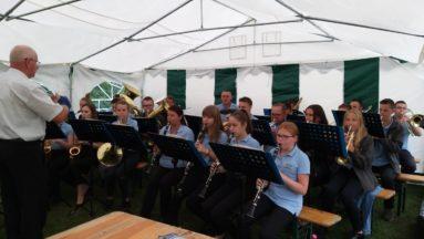 Zdjęcie przedstawia orkiestrę grającą w plenerze.