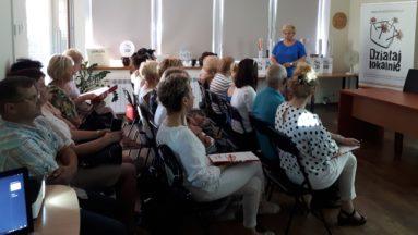 Zdjęcie przedstawia osoby siedzące na widowni.