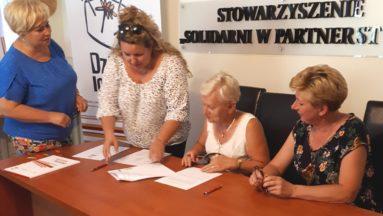 Zdjęcie przedstawia osoby przy stole we wnętrzu, podpisujące umowy.