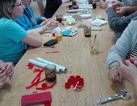 Zdjęcie przedstawia grupę osób siedzących przy stole, tworzących rękodzieło.