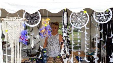 Zdjęcie przedstawia kobietę stojącą na stoisku na jarmarku, na którym wyłożone są produkty rękodzielnicze.