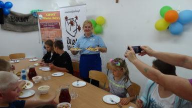 Zdjęcie przedstawia osoby przy stole, próbujące potraw.