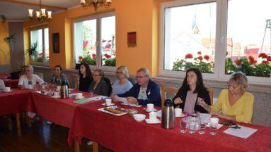 Zdjęcie przedstawia osoby siedzące przy stole, biorące udział w warsztatach dziennikarskich.