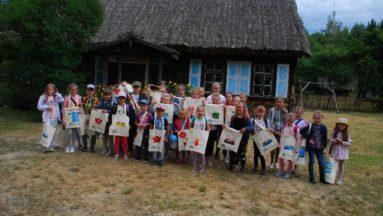 Zdjęcie przedstawia uzcestników projektu pozujących z wykonanymi przez siebie torbami.