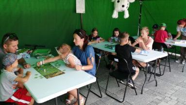 Zdjęcie przedstawia stoły ustawione w szeregu, przy których siedzą osoby grające w gry planszowe.