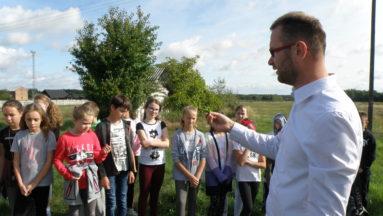 Prowadzący warsztaty opowiada dzieciom o roślinach rosnących na łące.