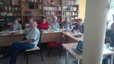 Zdjęcie przedstawia osoby słuchające wykładu w bibliotece.