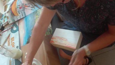 Zdjęcie przedstawia osobę dekorującą pudełko.