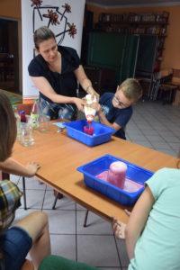 Na zdjęciu instruktorka pomaga osobie dziecięcej wwykonaniu eksperymentu-wulkanu.