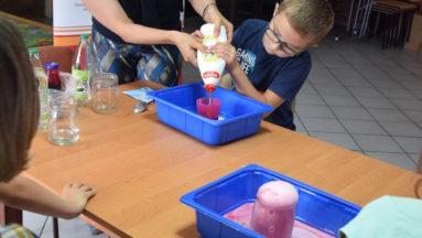 Na zdjęciu instruktorka pomaga osobie dziecięcej w wykonaniu eksperymentu-wulkanu.
