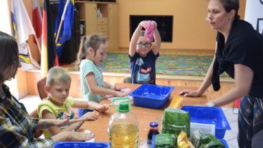 Na zdjęciu trójka dzieci oraz dwie instruktorki pracują przy stole z ciastoliną.