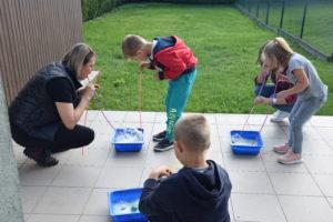 Zdjęcie przedstawia trójkę dzieci iinstruktorkę podczas ćwiczeń.